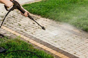 Person power washing patio pavers